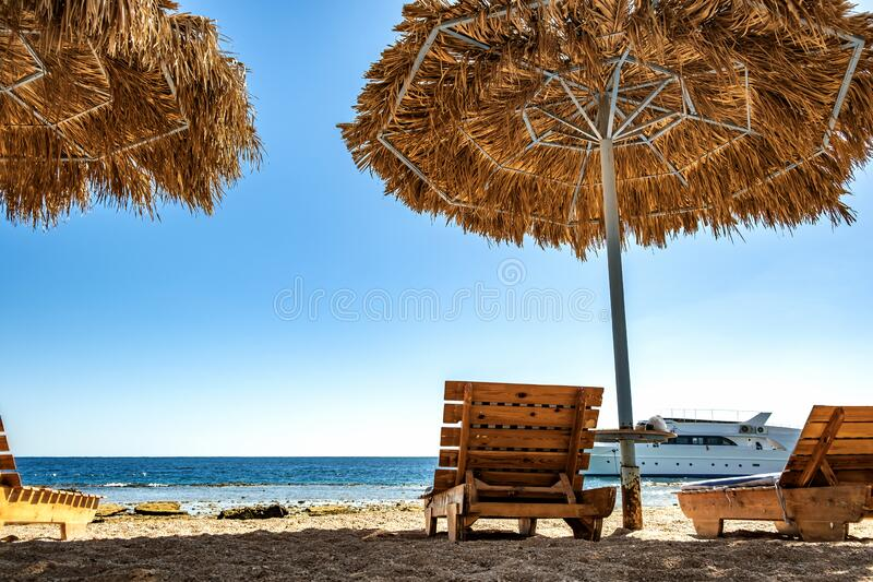 Wooden deck chairs under rough straw sun umbrella on sea beach and big white yacht ship in water near shore on sunny summer day.  stock images