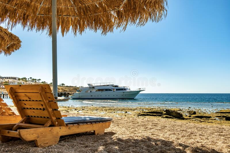 Wooden deck chairs under rough straw sun umbrella on sea beach and big white yacht ship in water near shore on sunny summer day.  stock photo