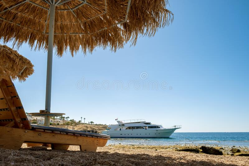 Wooden deck chairs under rough straw sun umbrella on sea beach and big white yacht ship in water near shore on sunny summer day.  stock photos