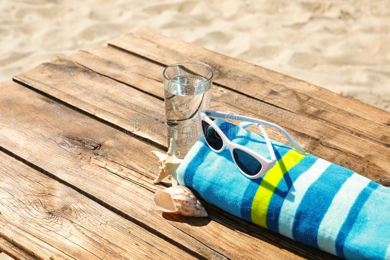 Wooden deck with glass of refreshing drink and beach accessories. On hot summer day stock photography