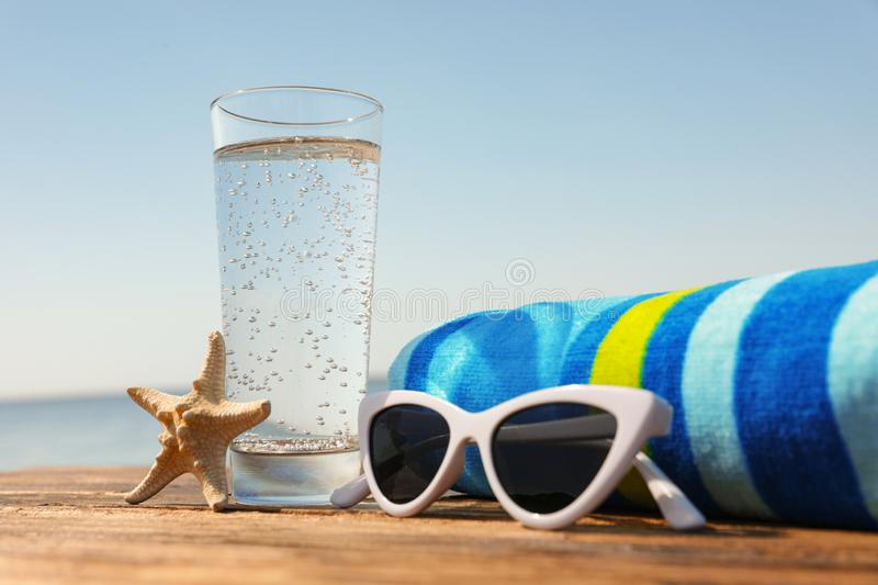 Wooden deck with glass of refreshing drink and accessories on hot summer day. Wooden deck with glass of refreshing drink and beach accessories on hot summer day royalty free stock image