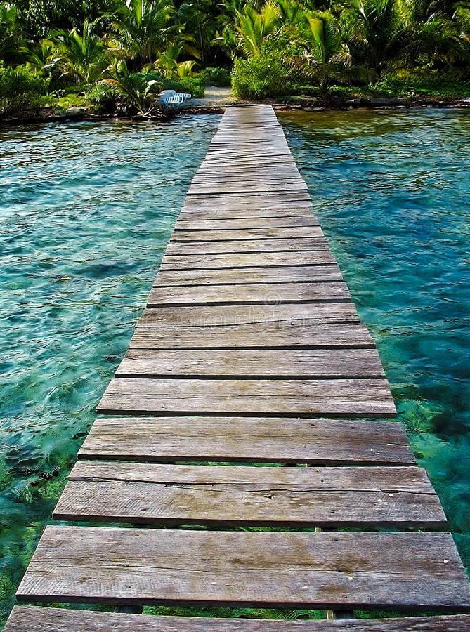 Wooden deck over tropical waters, connecting the bungalow to the beach. The long deck that connects the beach with our over water bungalow, blue-green waters in royalty free stock photos