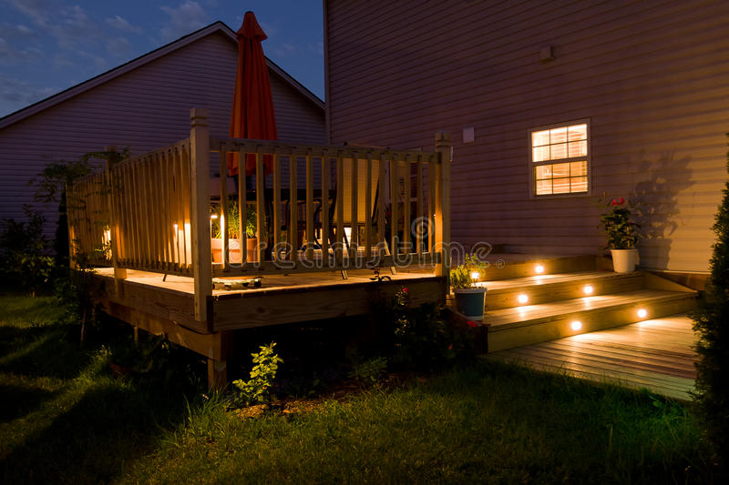 Wooden deck and patio of family home at night. Wooden deck and patio of family home at night with lights royalty free stock images