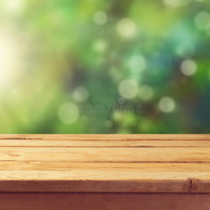 Wooden deck table with garden bokeh background. Ready for product display montage. royalty free stock image