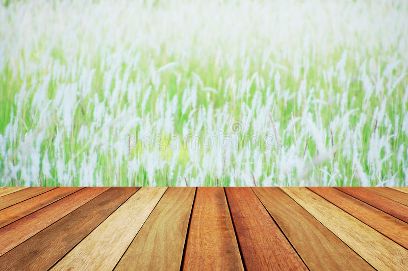 Wooden deck table over beautiful blurred grassland.  stock photography