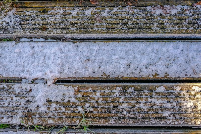Wooden decking covered with frost and light snow. Background graphic resource. Three wooden decking planks covered with light snow and frost. Background graphic stock photography
