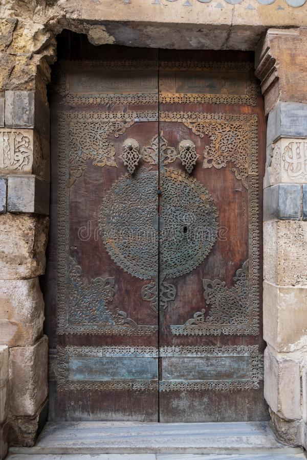 Wooden decorated copper plated door at Sultan Barquq mosque, Cairo, Egypt. Wooden decorated copper plated door leading to Sultan Barquq mosque, Al-Moez Street stock images