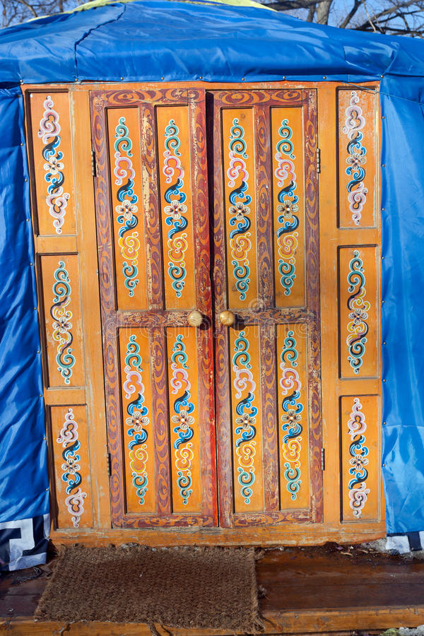 Wooden decorated orange door. In kazakh yurt royalty free stock photo