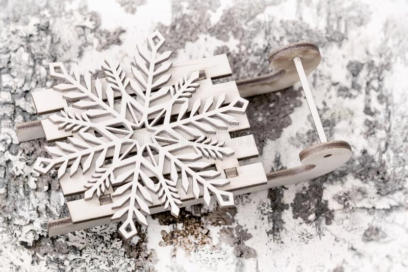 Wooden decoration, snowflake on little wooden sled close-up. Abstract blurred festive light Christmas background. Wooden decoration, snowflake on little wooden royalty free stock photo