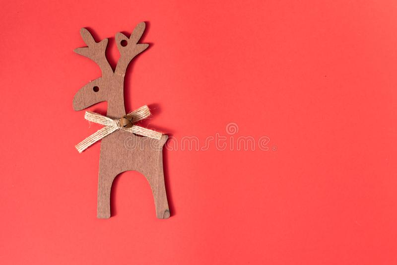Wooden deer decoration on red background. Christmas concept and New Year decoration. Top view, copy space royalty free stock images