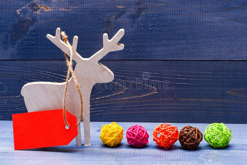 Wooden deer winter holiday decoration with tag for price on dark wooden background. Decorations for Christmas holidays royalty free stock image