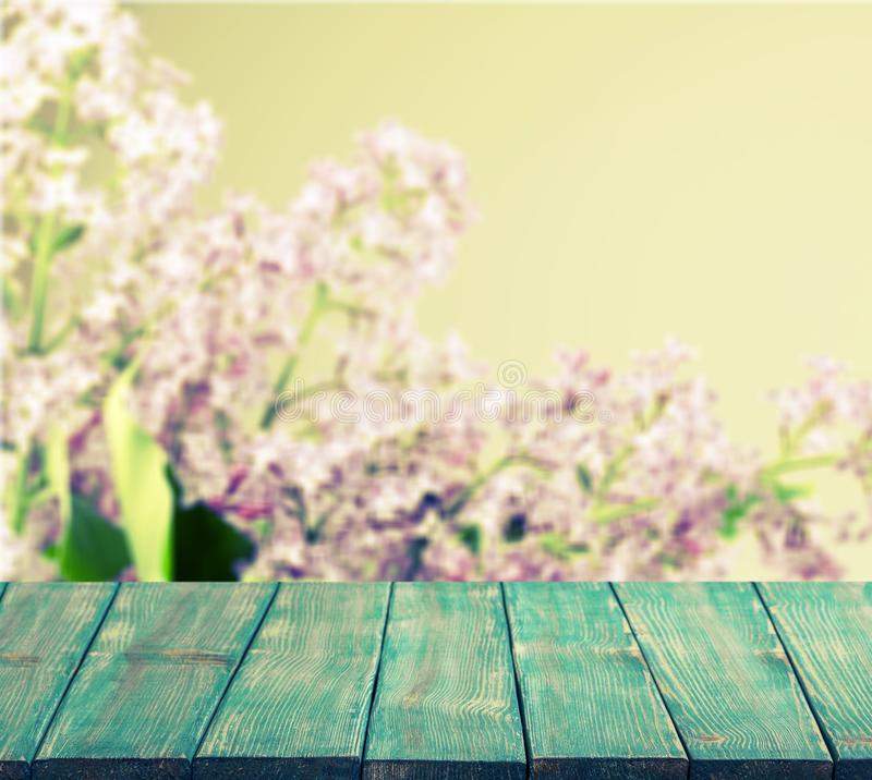 Wooden desk on flower background stock photos