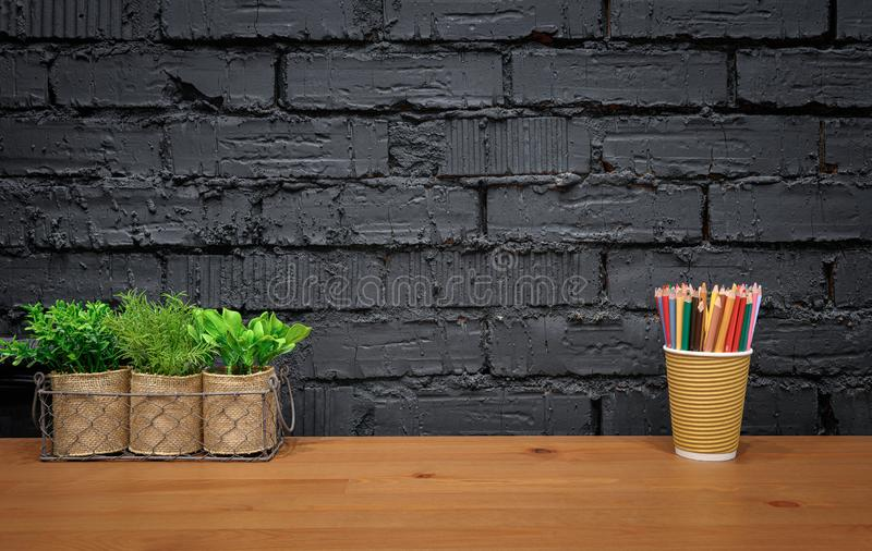 Stylish designer workspace. Wooden desk with house plants and color pencils on black brick wall background with copy space. Stylish designer workspace mockup royalty free stock photo