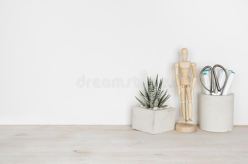 Wooden desktop with flower pot, human statuette and office supplies.  royalty free stock photography