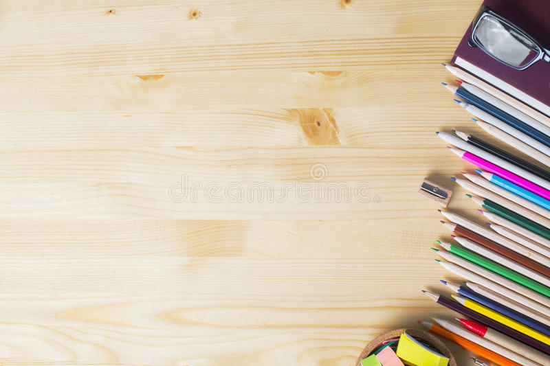 Wooden desktop with supplies. Top view of natural wooden desktop with colorful supplies. Mock up royalty free stock photo