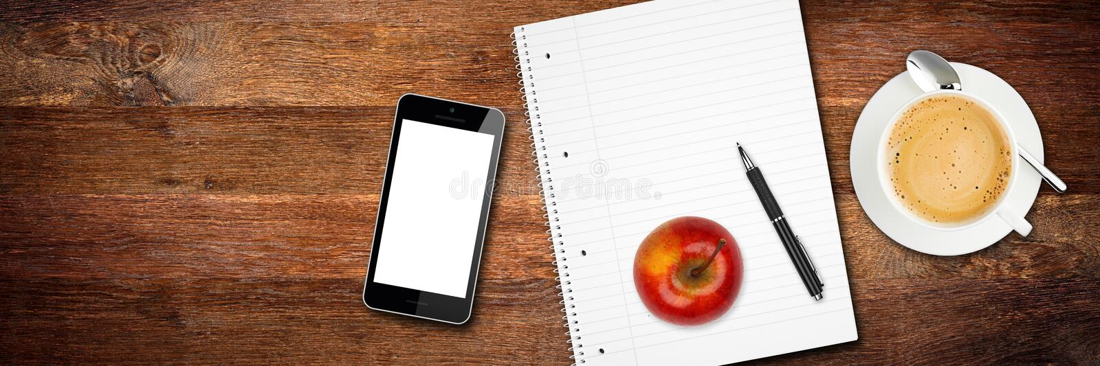 Wooden desktop tabletop view break. Concept with notepad smart phone apple pen and coffee cup royalty free stock image