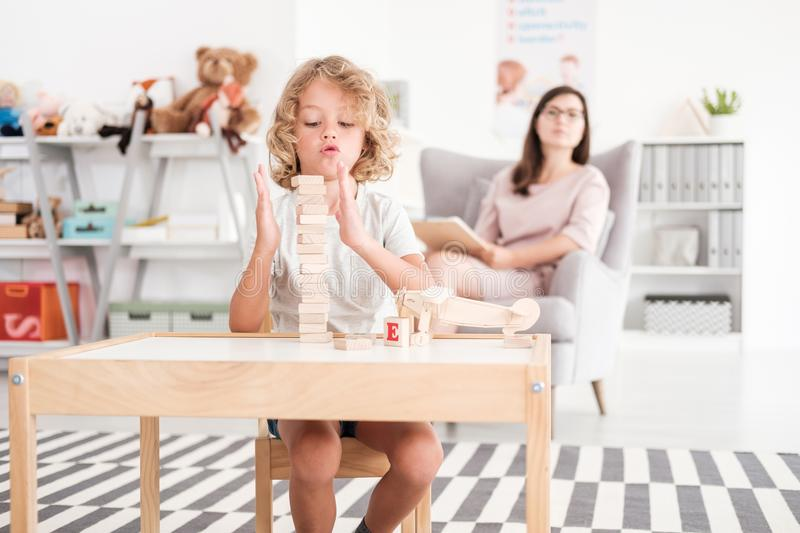 Wooden development props in the hands of a child during an educational therapy meeting with a pedagogue in a private medical offic. E royalty free stock photography