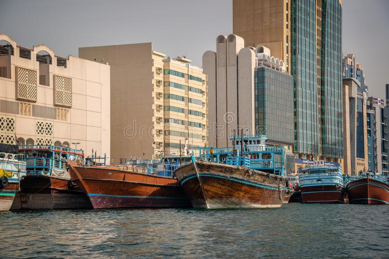 Wooden dhow cargo boats in Dubai Creek, modern buildings in the background, UAE royalty free stock images