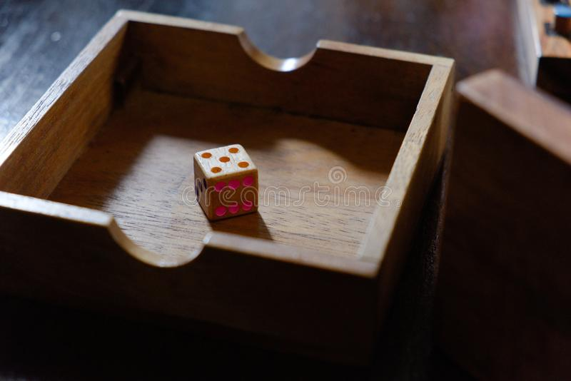A wooden dice in the box royalty free stock photography