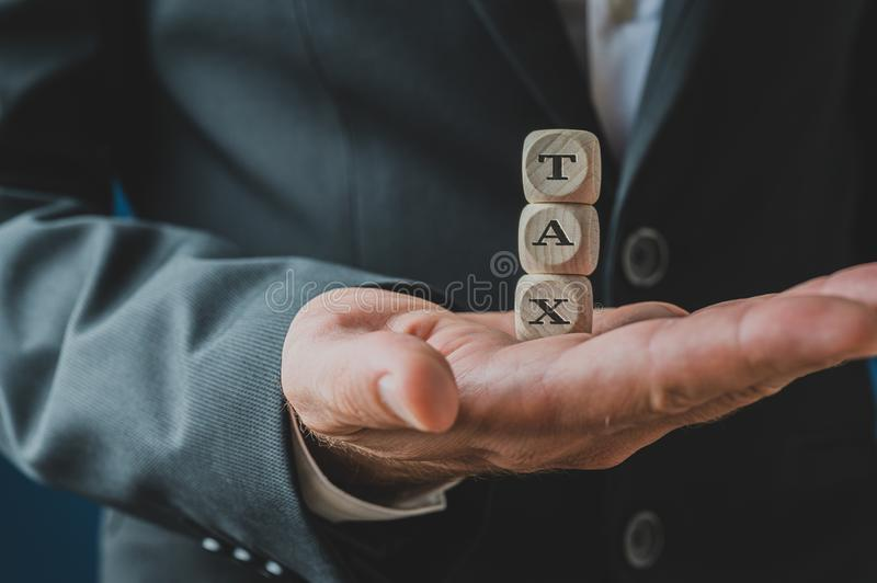Wooden dices spelling Tax. Businessman holding stacked wooden dices spelling Tax in his palm royalty free stock photos