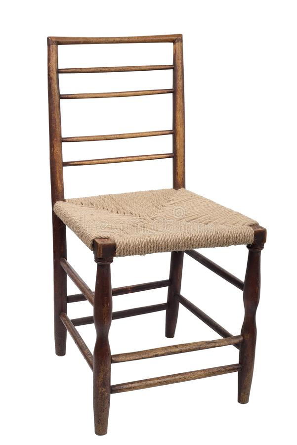Wooden dining chair , a crisscross back and against wicker woven seat royalty free stock images