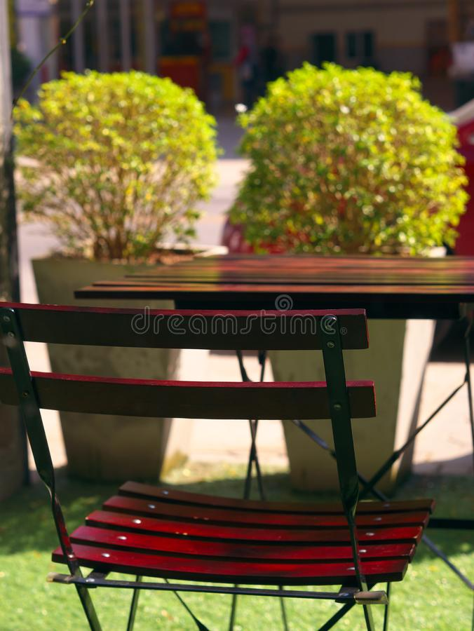 Wooden dining table and chair at green yard balcony in morning. royalty free stock image