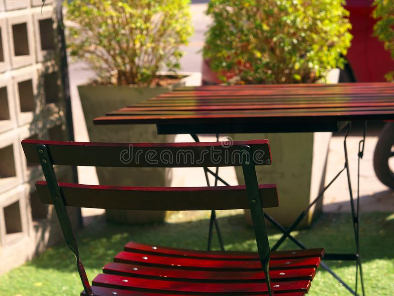 Wooden dining table and chair at green yard balcony in morning. stock images