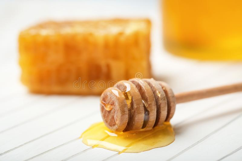 Wooden dipper with honey on table stock images