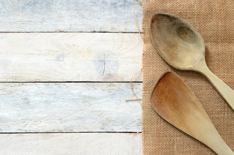 Wooden dipper kitchenware on a sack on a white wooden table royalty free stock photos