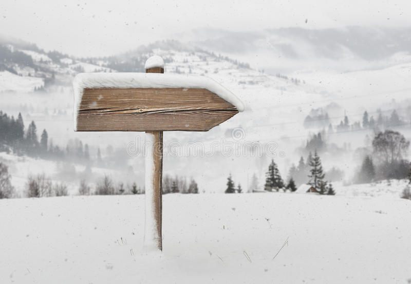 Wooden direction sign with less snow and mountains on background stock photo