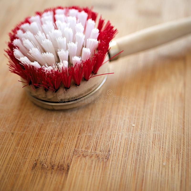 Wooden dish cleaning brush on wood grain table. Wooden dish cleaning brush on wood grain royalty free stock images