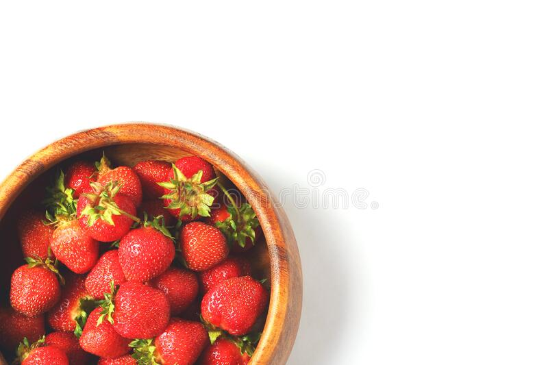 Wooden dish with strawberries. white background. View from the top stock image
