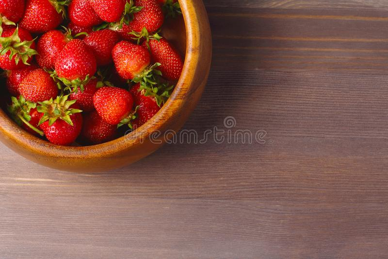 Wooden dish with strawberries. wood background, flat lay, space for a text royalty free stock photography