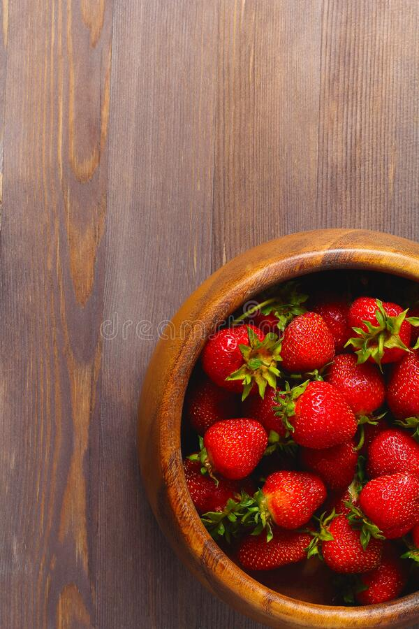 Wooden dish with strawberries. wood background, top view. Space for a text, vertical frame royalty free stock images