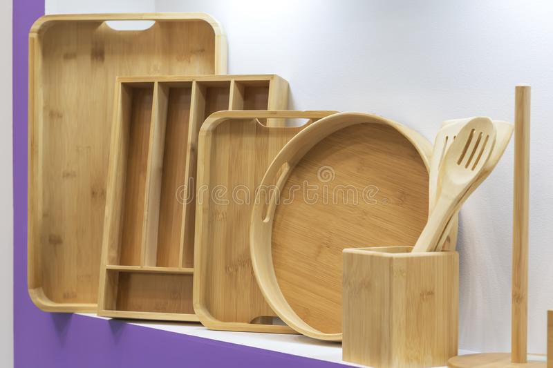Wooden dishes. Kitchen utensils and accessories made of bamboo. Eco-friendly products. Various salad bowls, dishes, plates, food. Trays and spoons on a stock photography