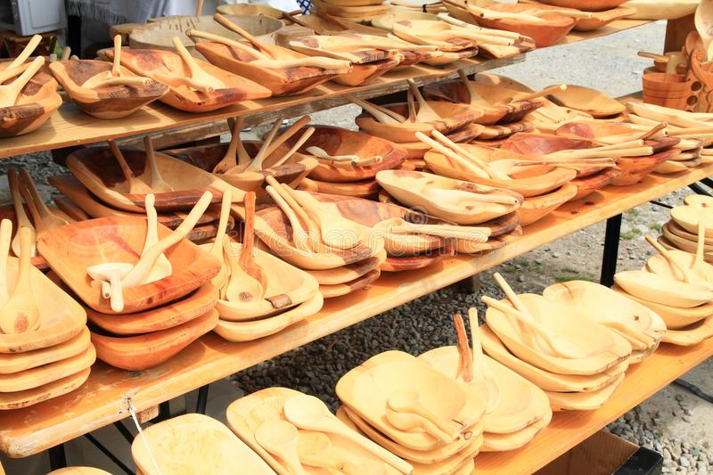 Wooden plates and spoons. Wooden dishes - plates and spoons on traditional market for sell stock images