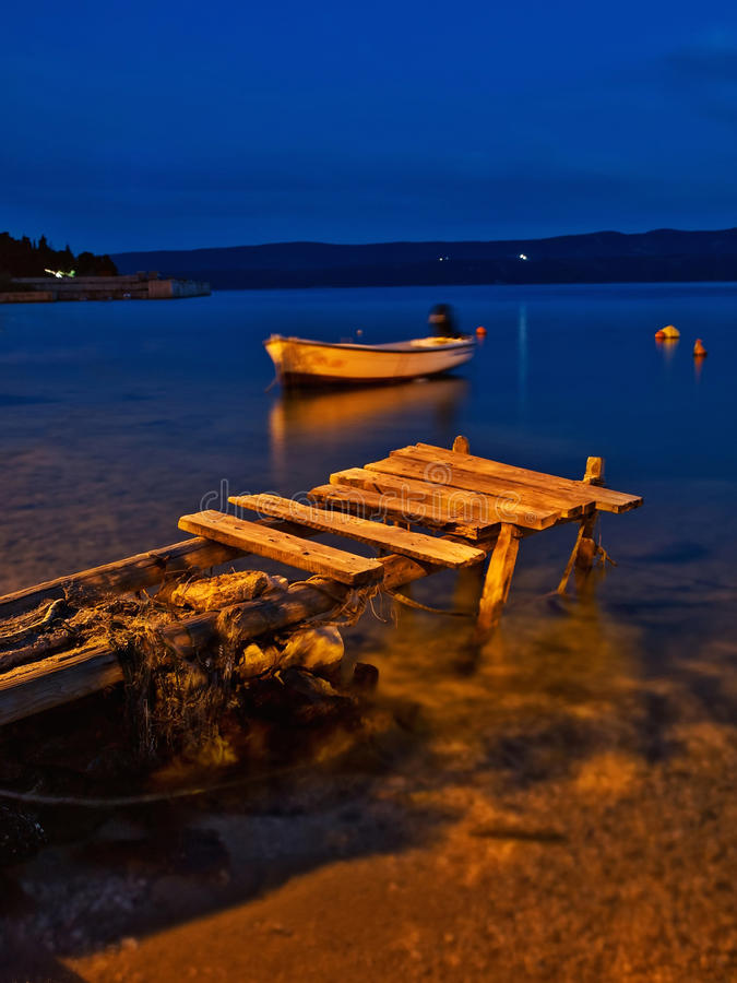 Wooden dock and boat at night stock images