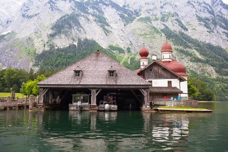 Wooden dock for boats with a temple and mountains in the background on Konigssee Lake, Austria.  royalty free stock photos