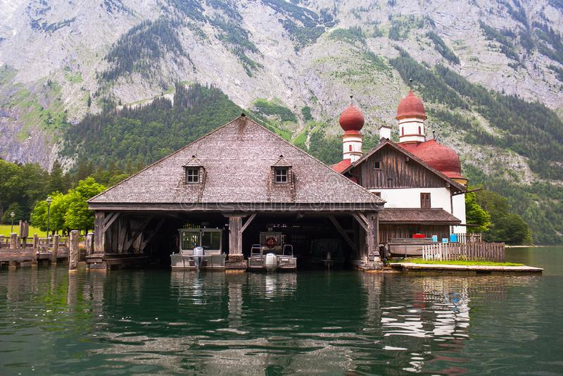 Wooden dock for boats with a temple and mountains in the background on Konigssee Lake, Austria.  royalty free stock images