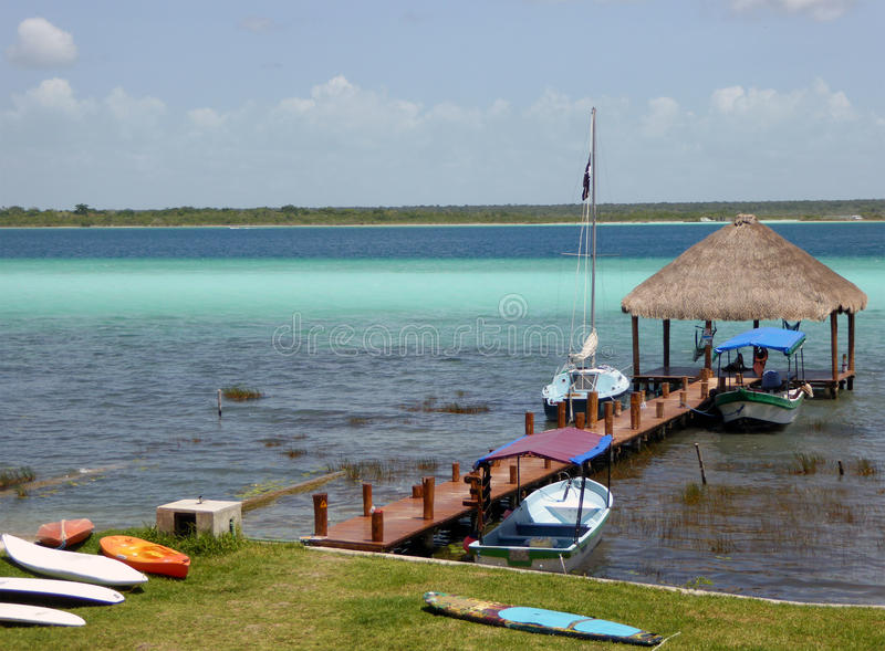 Wooden Dock with Boats on Tropical Lake Bacalar. A wooden indigenous-styled thatched dock with several boats and surf boards on the colorful, Caribbean-looking stock image