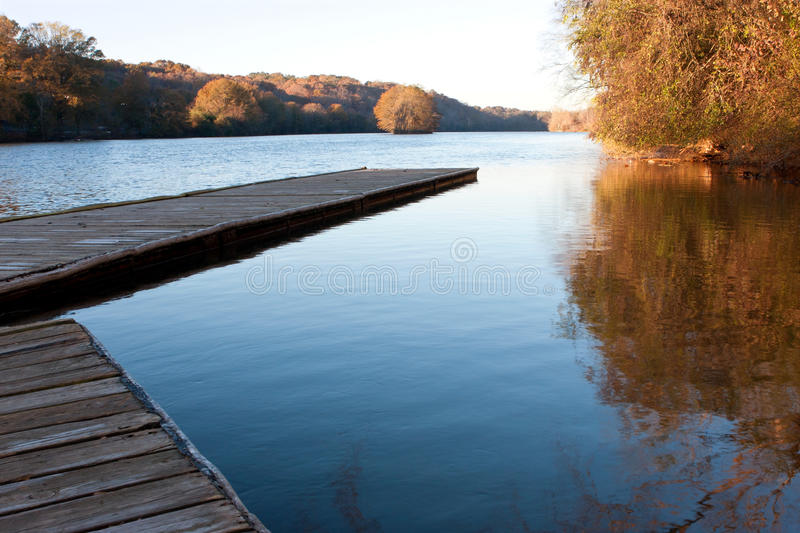 Wooden dock extends out into Atlanta's Chattahoochee River royalty free stock photography