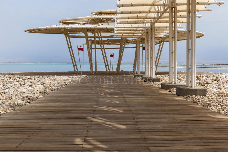 Wooden dock with shades and parasol royalty free stock image