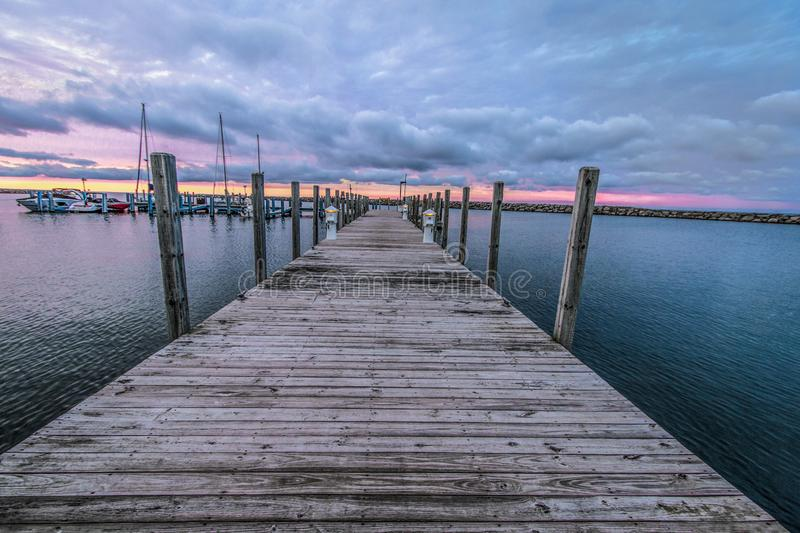 Long Wooden Pier At Sunset On The Michigan Great Lakes. Wooden Dock Sunset. Wooden dock disappears to the horizon with a sunset sky at the horizon royalty free stock photo