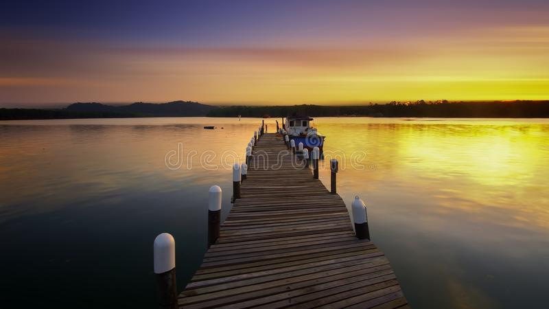 Wooden dock at sunset stock photo