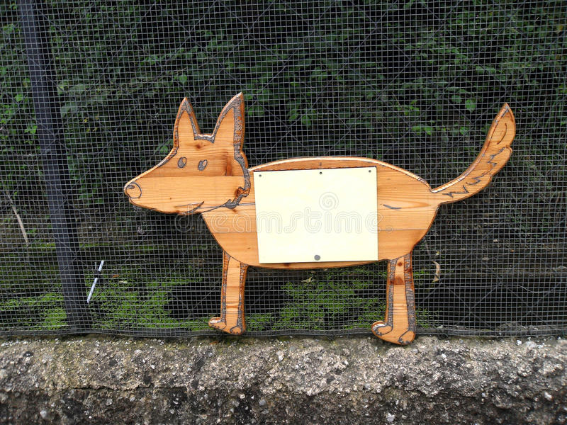 Wooden dog (fox) contour flat sign on the metal ne. T with small clean board on it royalty free stock photo