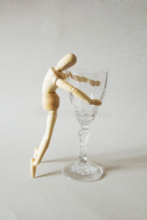 Wooden Doll Addict. Wooden Doll and Half Empty Glass of Wine. Alcoholism Concept stock image
