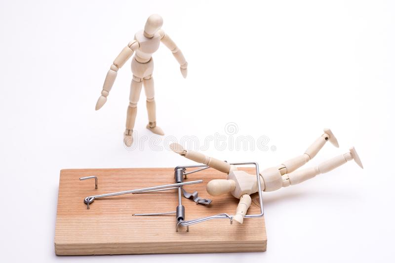 Wooden doll caught. In a mouse trap and bystander in front of white background royalty free stock images