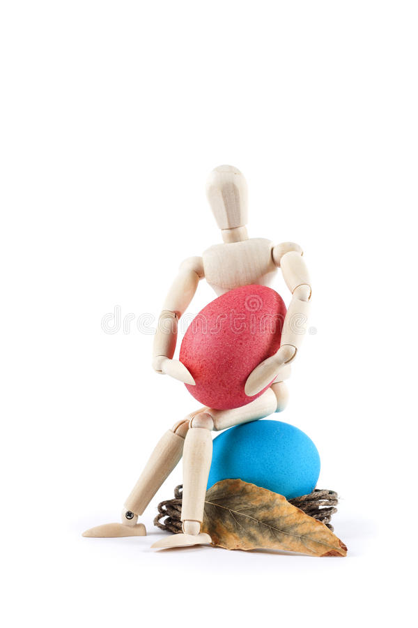 Wooden doll holding easter egg on white background royalty free stock images