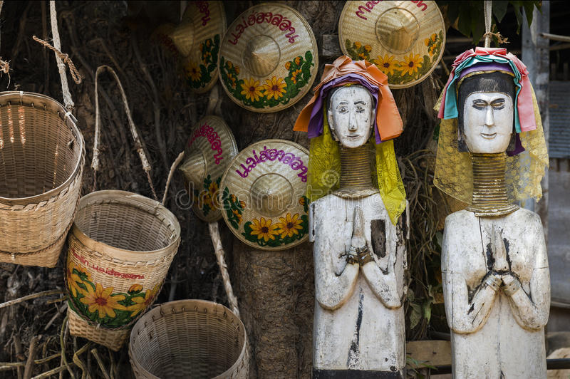 Wooden Dolls of Karen long neck hill tribe. The village in north of Thailand, acting as welcome to visit. Wording on the hats and baskets are Thai language stock images