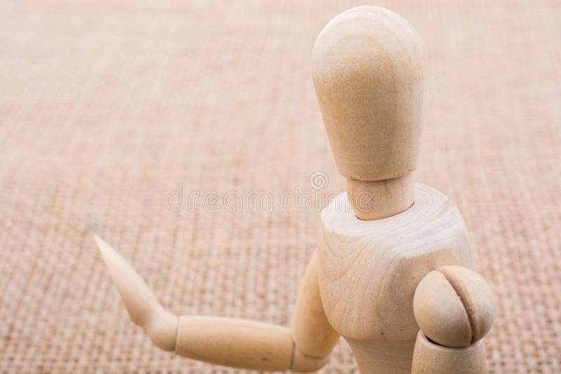 Wooden dolls posing on canvas. Wooden dolls of a man posing on canvas stock photo